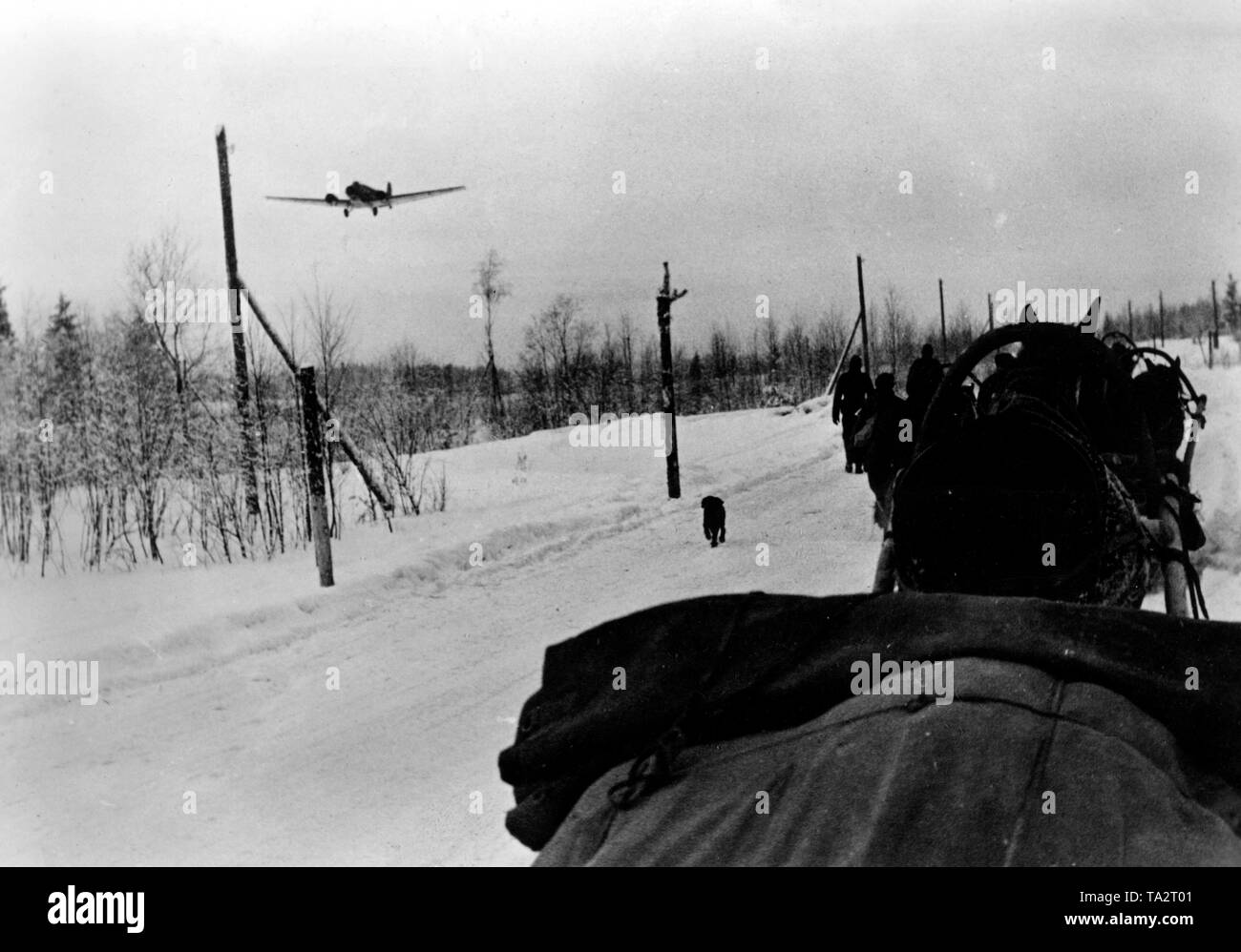 A Junkers Ju 52 crosses a German column near Demjansk. The photo was taken in front of the complete encirclement and the associated airlift. Photo of the Propaganda Company (PK): war correspondent Beissel. - Stock Image
