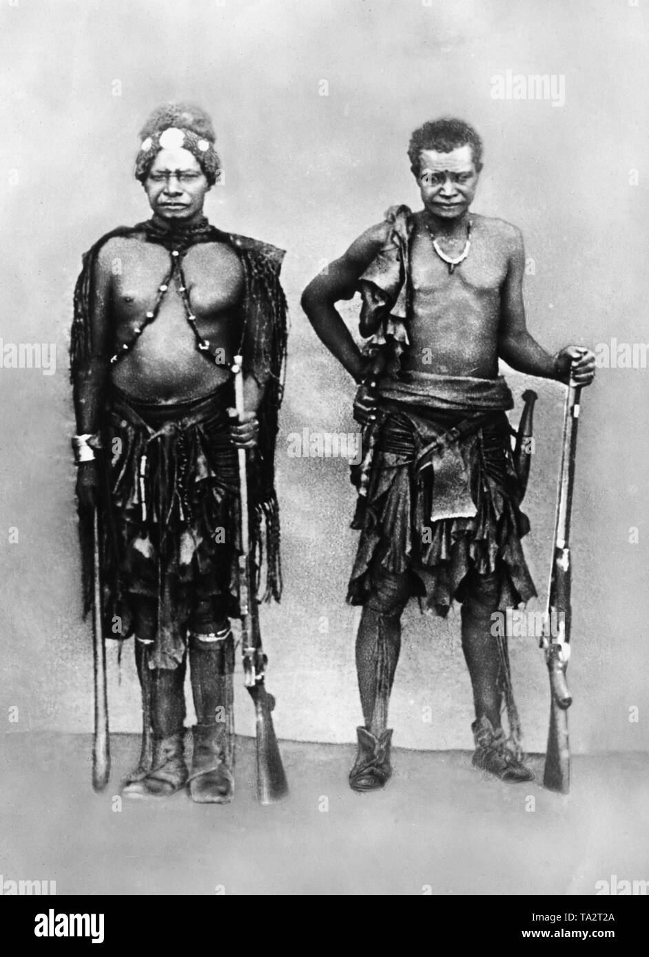 Herero chief Kambazembi wa Kangombe, a tribal leader of the Herero, the man on the right next to him is unknown. Both wear traditional clothing, jewelry and guns (undated shot). - Stock Image