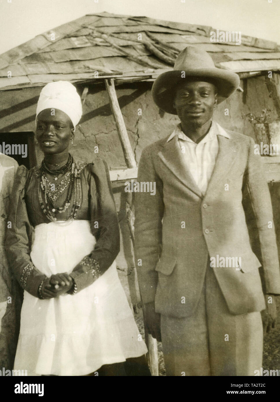 Two natives (a woman and a man) in European clothes in front of a hut in German Southwest Africa. (undated photo) Stock Photo