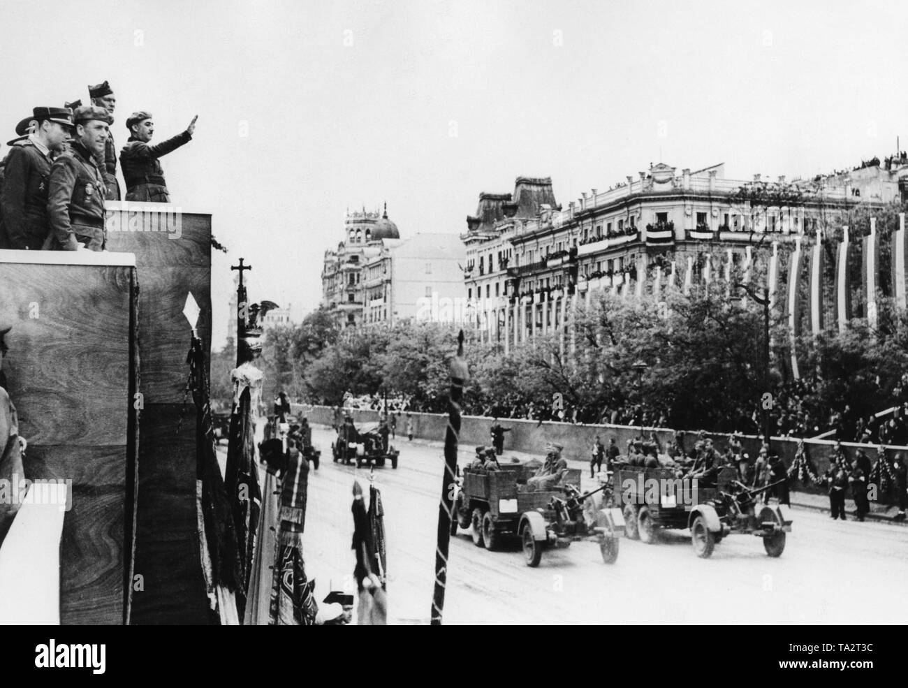 Photo of the luxury district of Paseo del la Castellana in Madrid during the great victory parade of the Spanish national troops in Madrid on May 19, 1939. On the left in the edge of the photo,the Caudilo General Francisco Franco (on the right with his arm raised) and major general Freiherr Wolfram von Richthofen along with other high officers are inspecting the parade from a stage. On the right, an anti-aircraft unit defiles (Krupp L2 H143 tractor with 2cm flak 30). - Stock Image