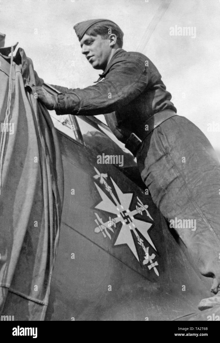 Photo of a German soldier of the ground personnel, who uncovers a Messerschmitt Bf 109 during the air battles of England in October 1940. On display the Spanish Cross, which was awarded by Adolf Hitler to the fighters of the Condor Legion in the Spanish Civil War, 1939. - Stock Image
