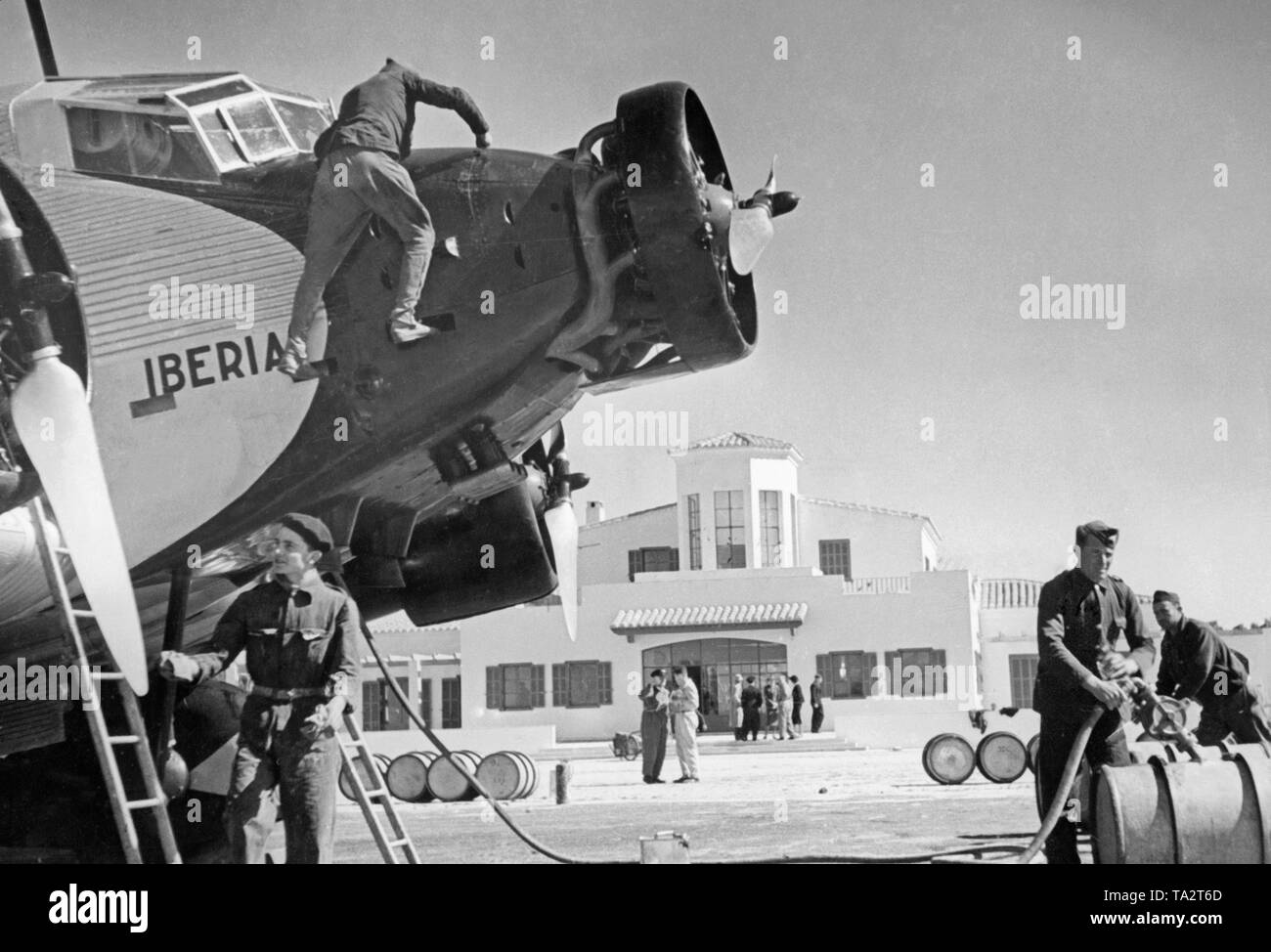Photo of the cockpits and engines of a German Junkers Ju 52 of the Spanish airline Iberia 1939 at the airport of Salamanca, Castile and Leon, Spain. Mechanics are working on one of the engines. The machine is named 'Mola', after general Emilio Mola Vidal (died 1937), one of the leaders of the uprising of General Francisco Franco. During the Civil War, the Deutsche Lufthansa and the Iberia (founded in 1927) carried out scheduled flights mostly with German pilots in the Spanish national zone from 1937. The aircraft were provided by the Deutsche Lufthansa AG. - Stock Image