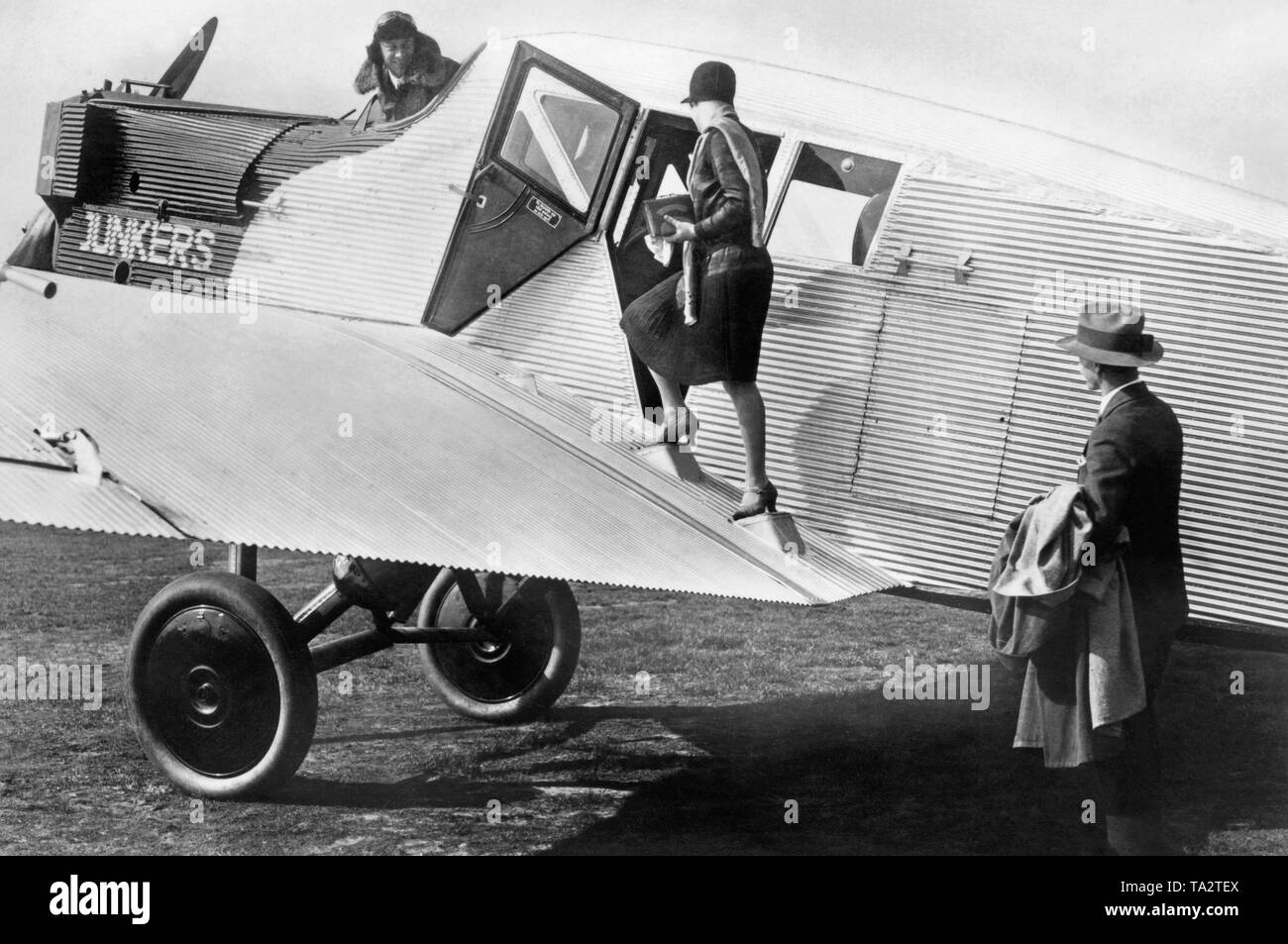 A woman climbs a Junkers F13 of Junkers Luftverkehr AG. The F13 was the first passenger aircraft made entirely of metal. The Junkers Luftverkehr AG merged with the German Aero Lloyd into the Deutsche Luft Hansa AG. - Stock Image