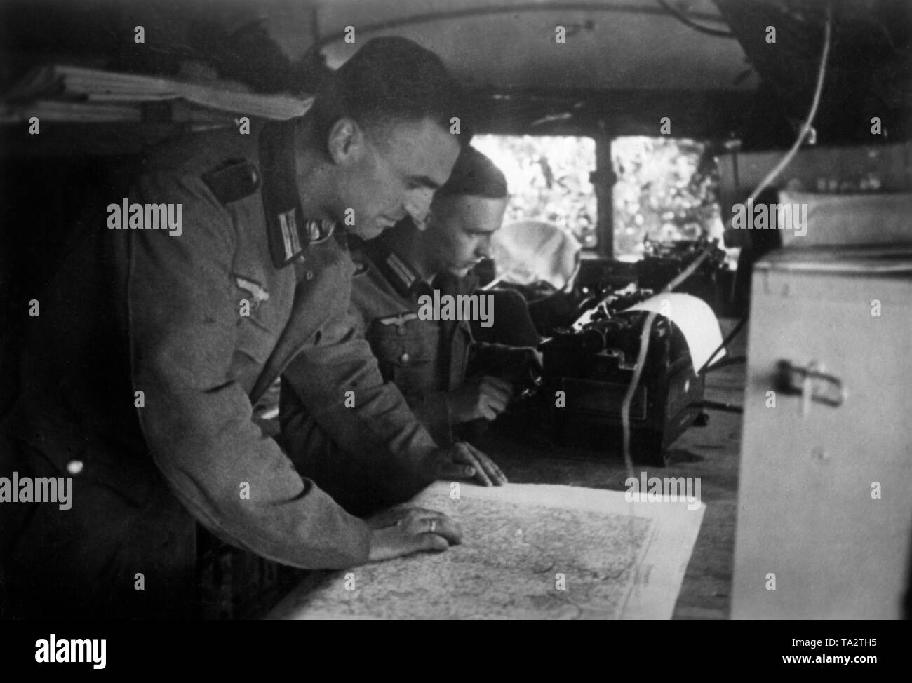 New results of the reconnaissance are compared with old maps. Photo: war reporter Utecht. Stock Photo