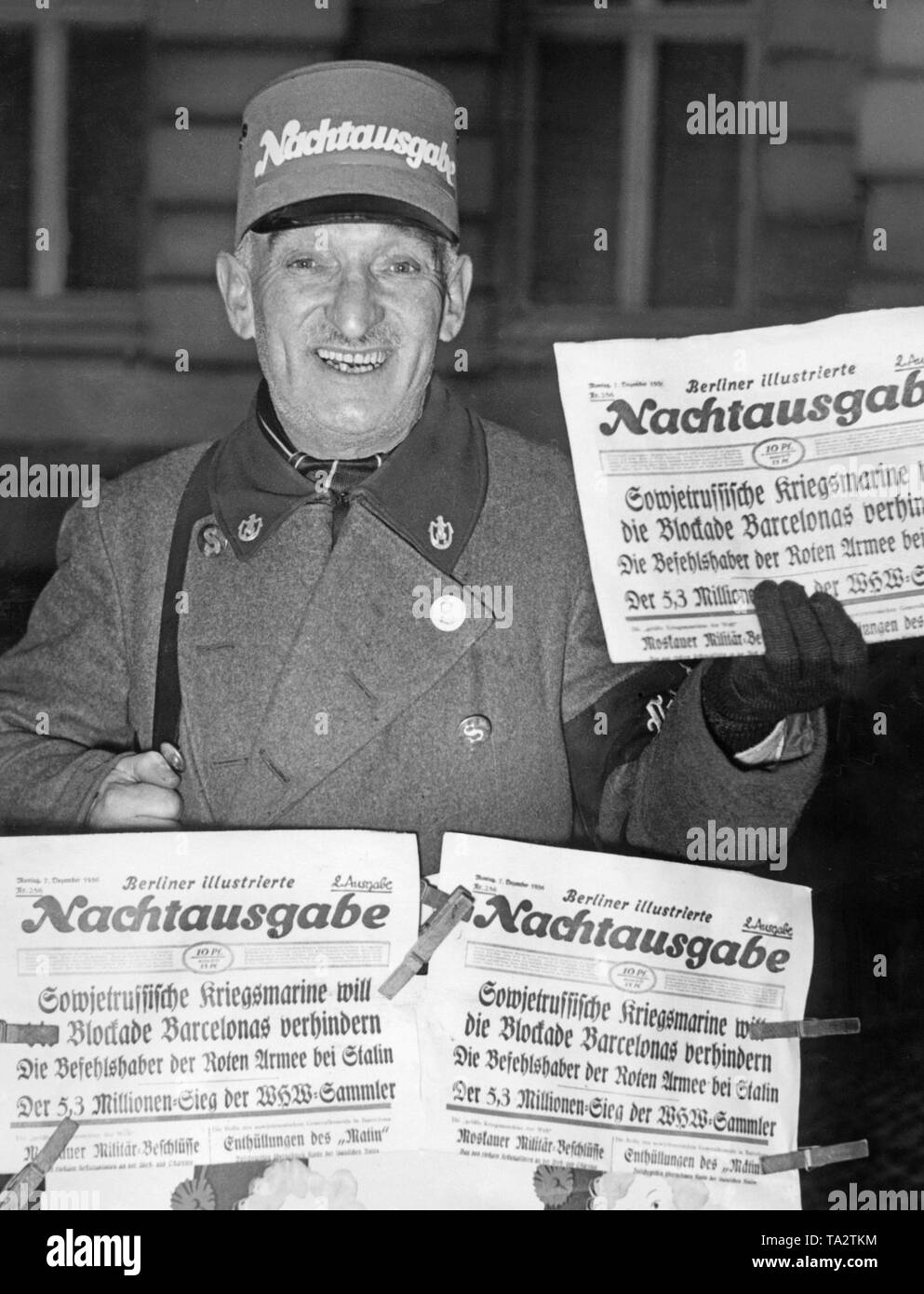 Photo of a newspaperman of the 'Illustrierte' with the late-night edition of the newspaper on December 7, 1936 in Berlin. The headline about the Spanish Civil War: 'Soviet Kriegsmarine (military navy) wants to prevent the blockade of Barcelona'. The Republican newspaper had been supported by the Soviet Union since the summer of 1936 with a supply of weapons and voluntary fighters. The nationalist troops also received international support. - Stock Image