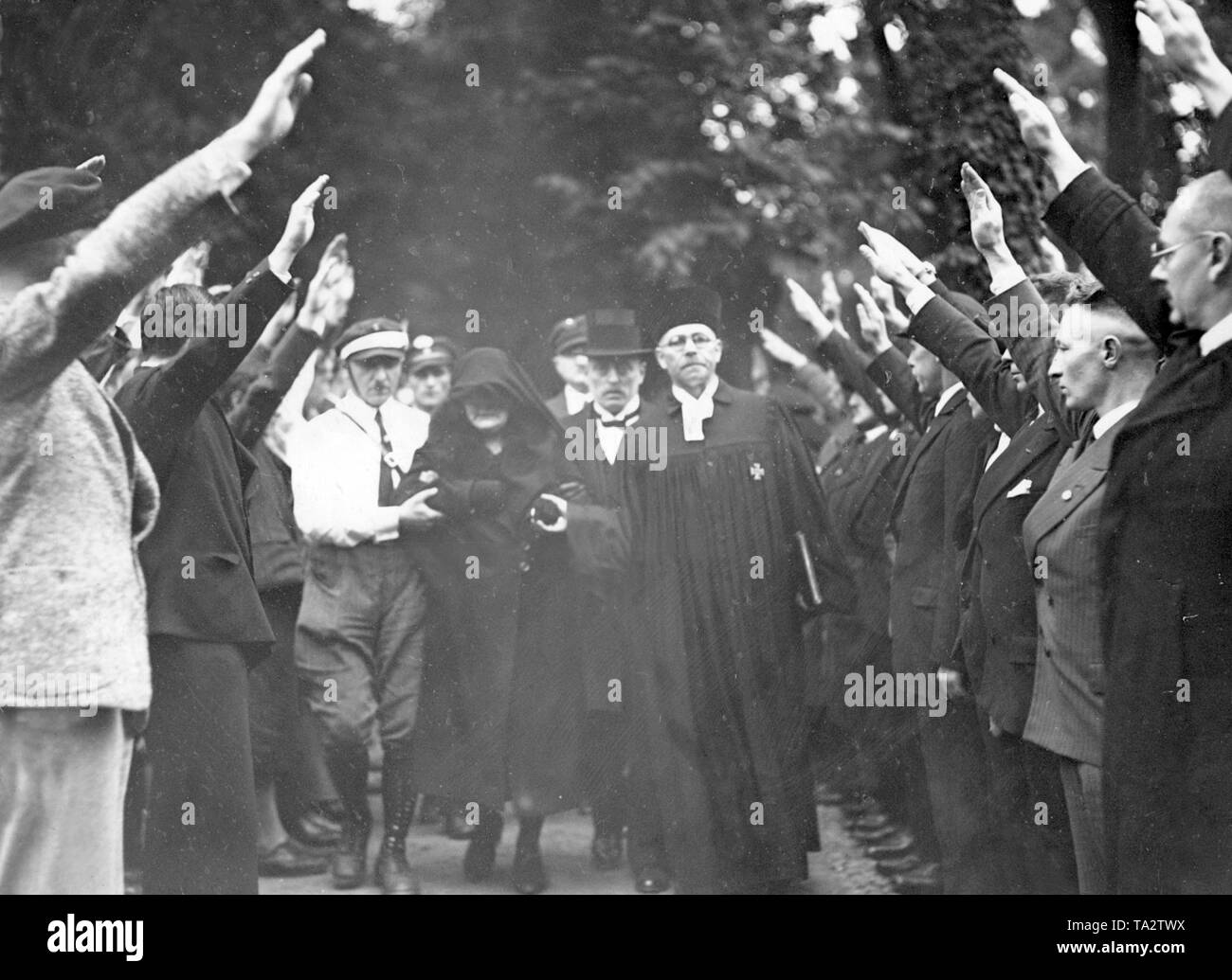 Burial of Herrmann Tielsch, murdered by the Communists, in the municipal cemetery at Bergmannstrasse in Berlin. The parents of the victim walk along with the clergymen and the guards of honor. The participants show the Hitler salute. - Stock Image