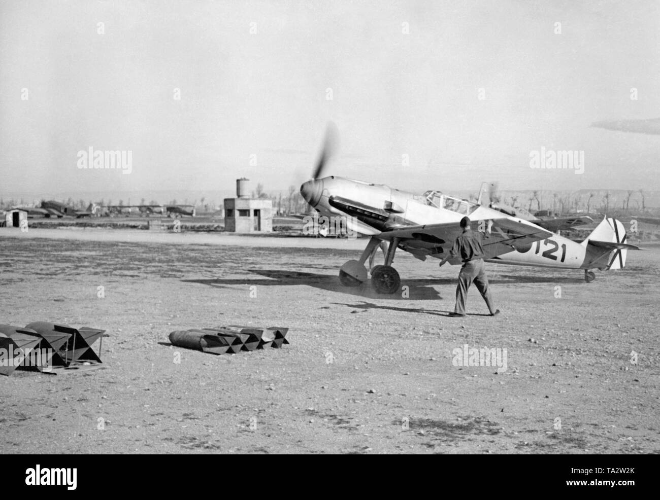 Photo of a German fighter, type Messerschmitt Bf 109, of the Fighter Squadron 88 of the Condor Legion during a take-off on a Spanish airfield. At the rear there is the saltire of the Spanish Air Force. In the background there are buildings and other aircrafts: Junkers Ju 52, Fieseler Storch. In the foreground are aerial bombs. - Stock Image