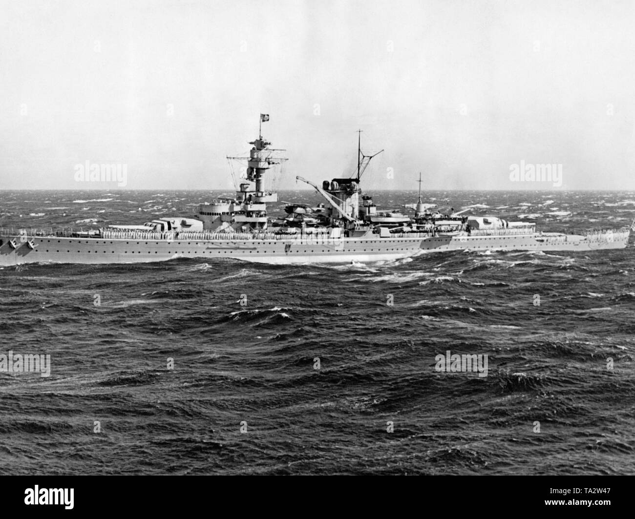 Photoof theheavy cruiser'Deutschland' in astormy sea taken by a photographer of the fleet of theNazi organization 'Kraft durch Freude' ('Strength through Joy') during a KdF trip off theItalian coast on the 7th of November, 1937. The crewhas lined upon the deck. At thebow and at therear therearetwo turretswith six 28 cmquick-fire guns. In the middle, one of the twoshipaircrafts of the typeArado Ar 196. - Stock Image