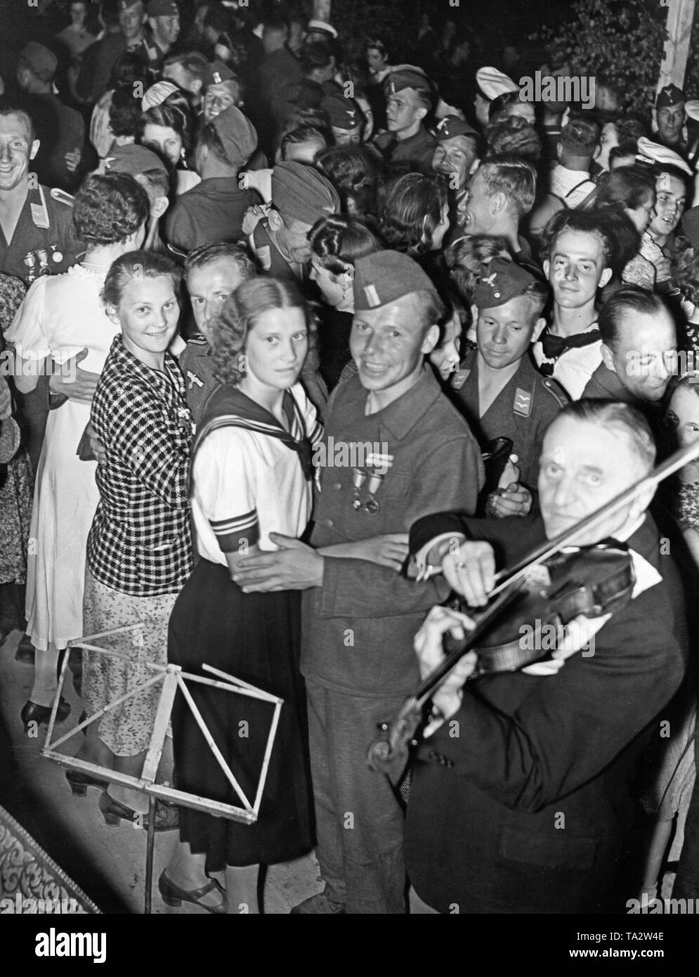 Photo of a group of soldiers of the Condor Legion (army and air force) in uniform and women from Berlin during a dance after the victory parade of the troop in Mitte (Berlin) on the evening of June 6, 1939, in Doeberitz. The cheerful bivouac was organized by the Legion and the NSG 'Kraft durch Freude' (Nazi Organization 'Strength through Joy'). There were bivouac bonfire, open-air performances and firework. In the foreground is a violinist. - Stock Image