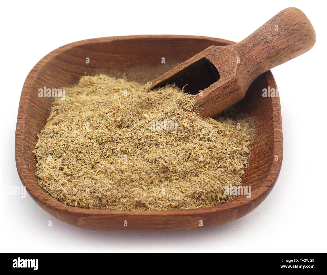 Liquorice stick and ground powder in a bowl over white - Stock Image