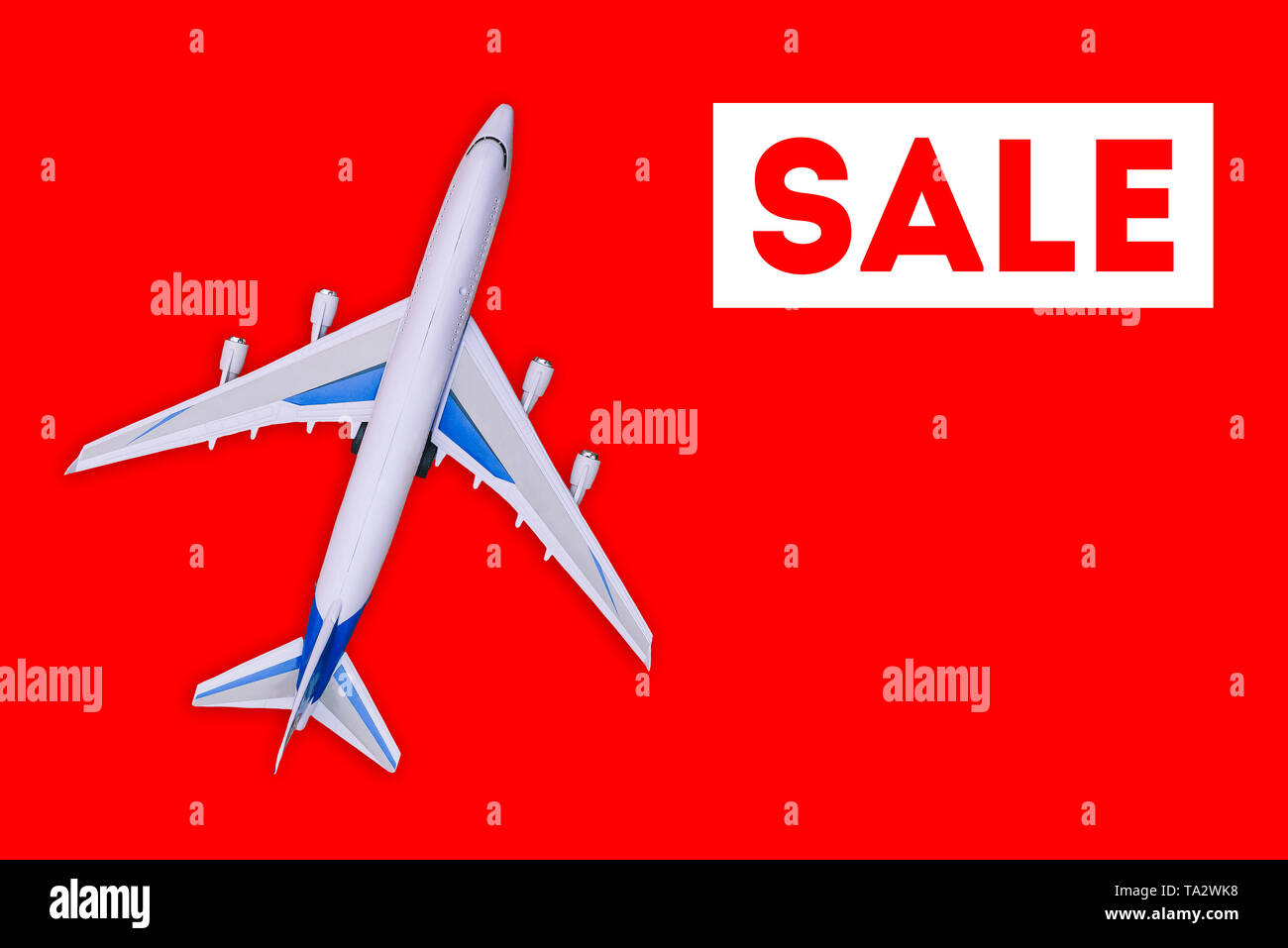 Travel and tourism concept. . Sale of air tickets and travel vouchers. Passenger aircraft on a red background - Stock Image