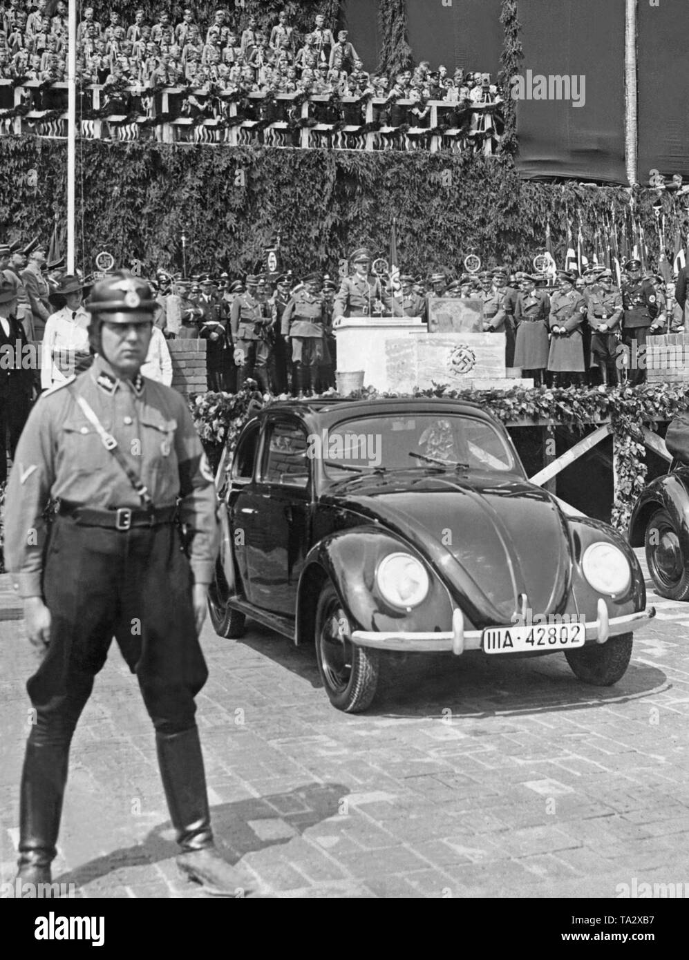 Hitler during his speech at the groundbreaking ceremony of the VW plant in the 'Stadt des KdF-Wagens' (City of the KdF Car), the later Wolfsburg. In the foreground, a soldier and two prototypes of the car. - Stock Image