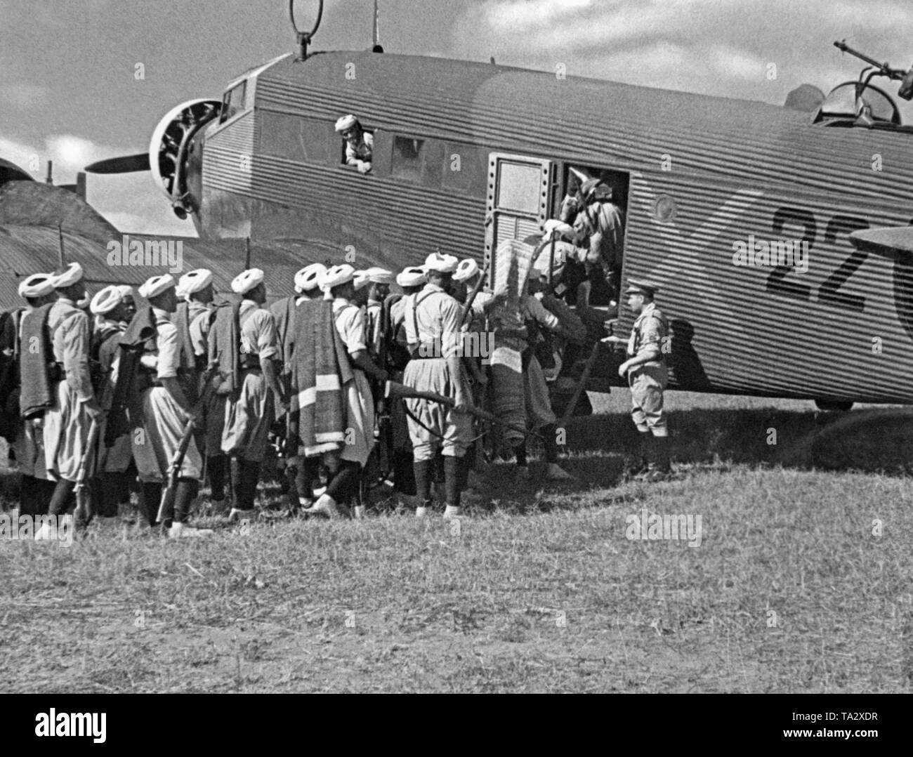 The photo shows Moroccan soldiers of the Spanish Foreign Legion with a German Junkers Ju 52 transport aircraft with the paintwork of the German Condor Legion. The soldiers were to fly from Tetouan, Spanish-Morocco, Africa, to the Spanish mainland in the summer of 1936. On the right at the top, the on-board weapon (MG 34) against enemy fighters. After the outbreak of the Spanish Civil War on July 27, 1936, Germany provided military assistance to General Franco (Operation Feuerzeauber). In addition, 20 Ju-52s (mostly Lufthansa aircrafts) were provided, which flew more than 800 flights of - Stock Image