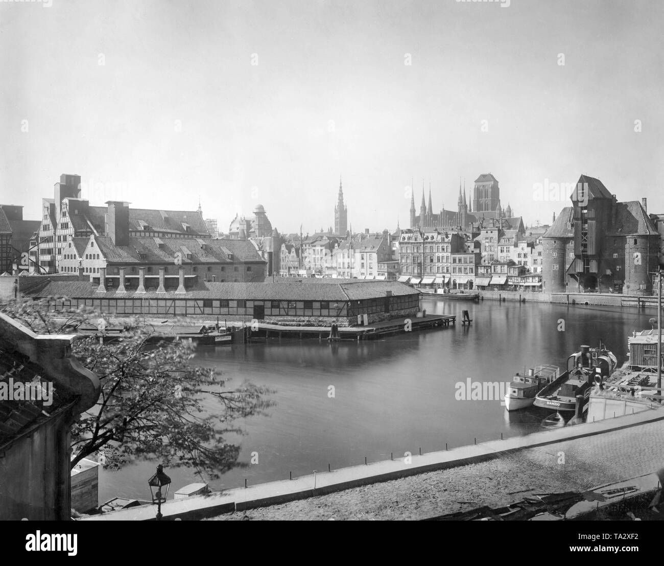 This photograph shows an overview of the port of Danzig, right the port crane to its left, St. Mary's Church. - Stock Image