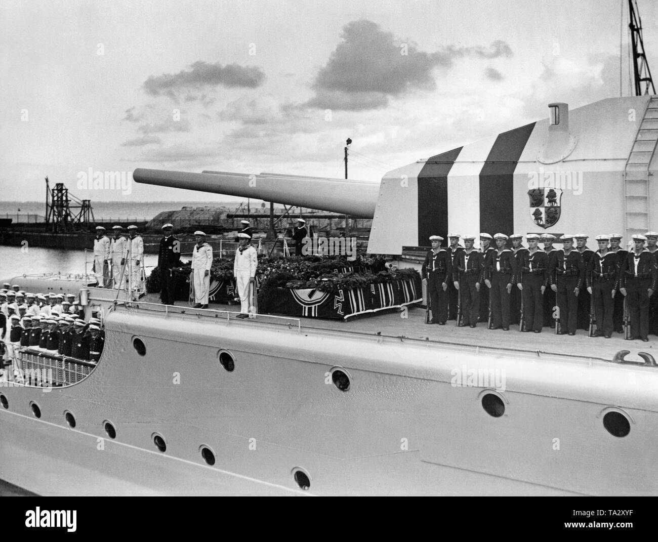Photo of the upper deck of the heavy cruiser 'Deutschland' with the coffins of its crew members, who were killed in the bombing of republican aircrafts during the Spanish Civil War near Ibiza in June 1937, in the port of Wilhelmshaven on the North Sea. Beside the coffins adorned with the naval ensign and floral wreaths, the garrison has lined up in dress uniforms. Behind, there is the turret with three gun barrels (caliber 28cm). In the background, the harbor installations. - Stock Image