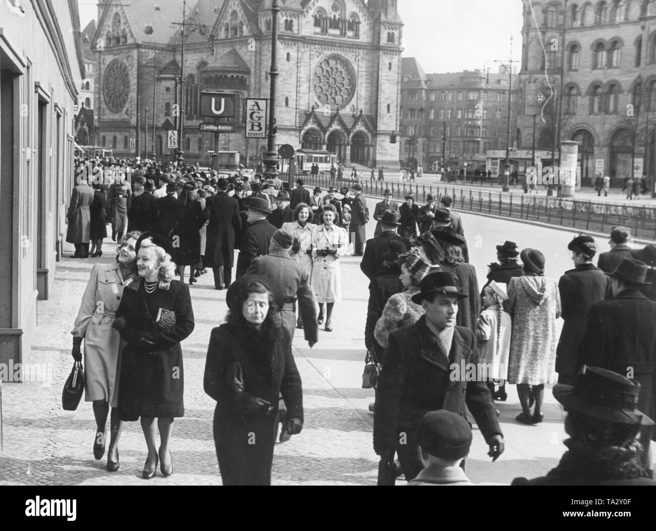 Passers-by walk through the Hardenbergstrasse in Berlin at Easter. In the background the Kaiser Wilhelm Memorial Church. - Stock Image