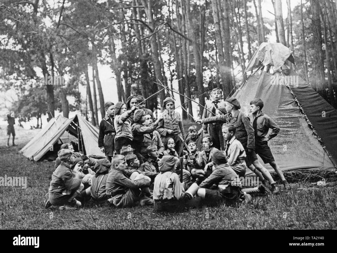 Boys sit together in a tent camp and fight playfully with sticks. - Stock Image