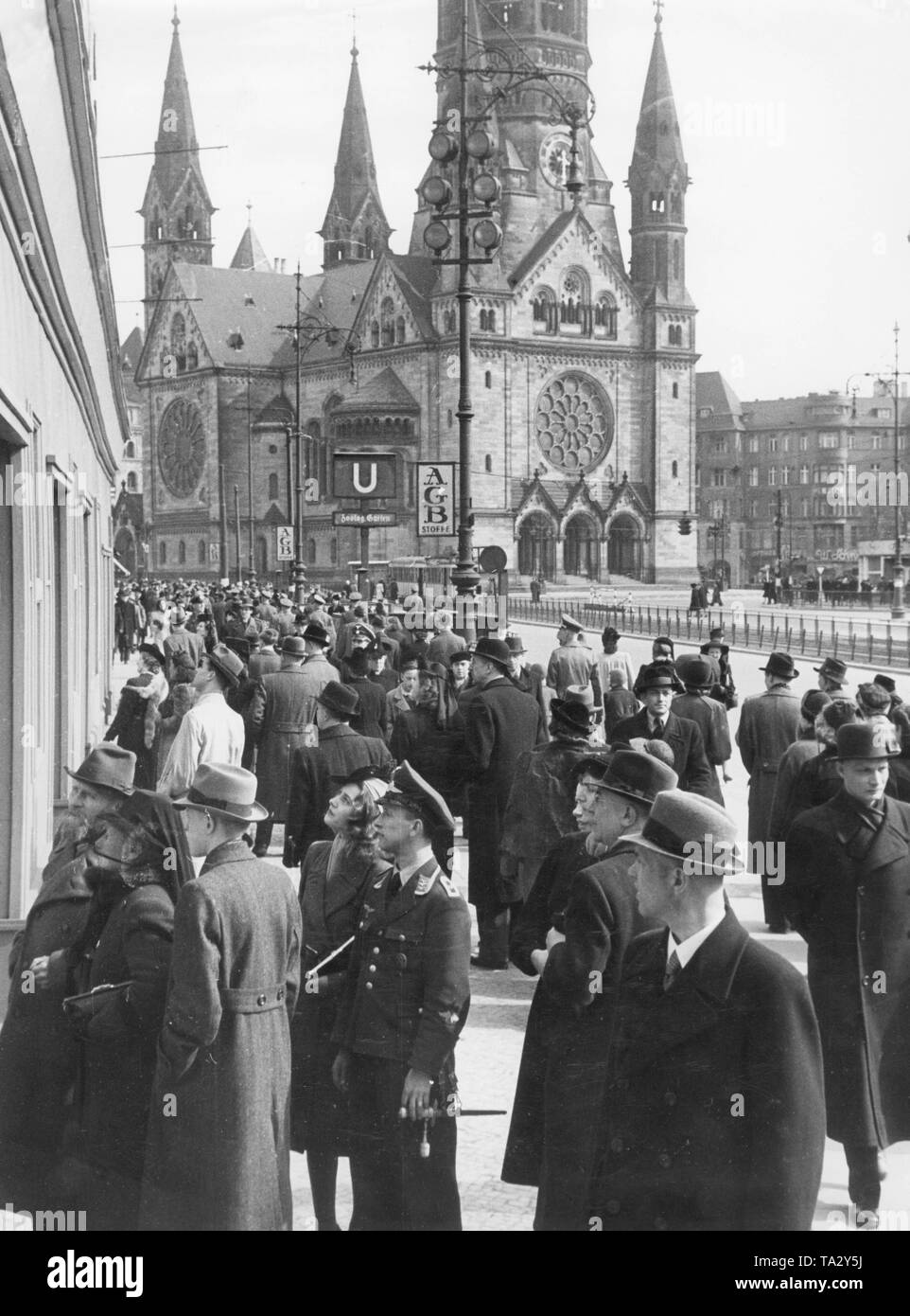 Passers-by walk through the Hardenbergstrasse in Berlin at Easter. In the background the Kaiser Wilhelm Memorial Church. In front is a member of the Luftwaffe with his girlfriend. - Stock Image