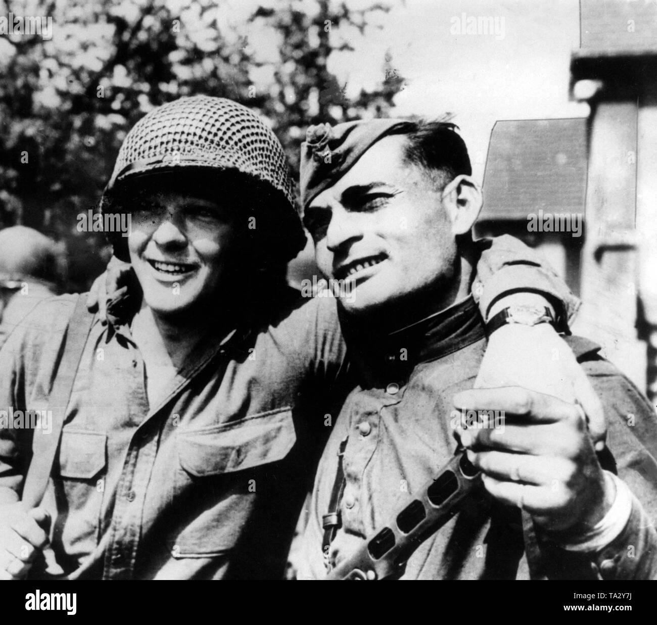 An American (left) and a Soviet soldier during a meeting of the two armies in Torgau. Stock Photo