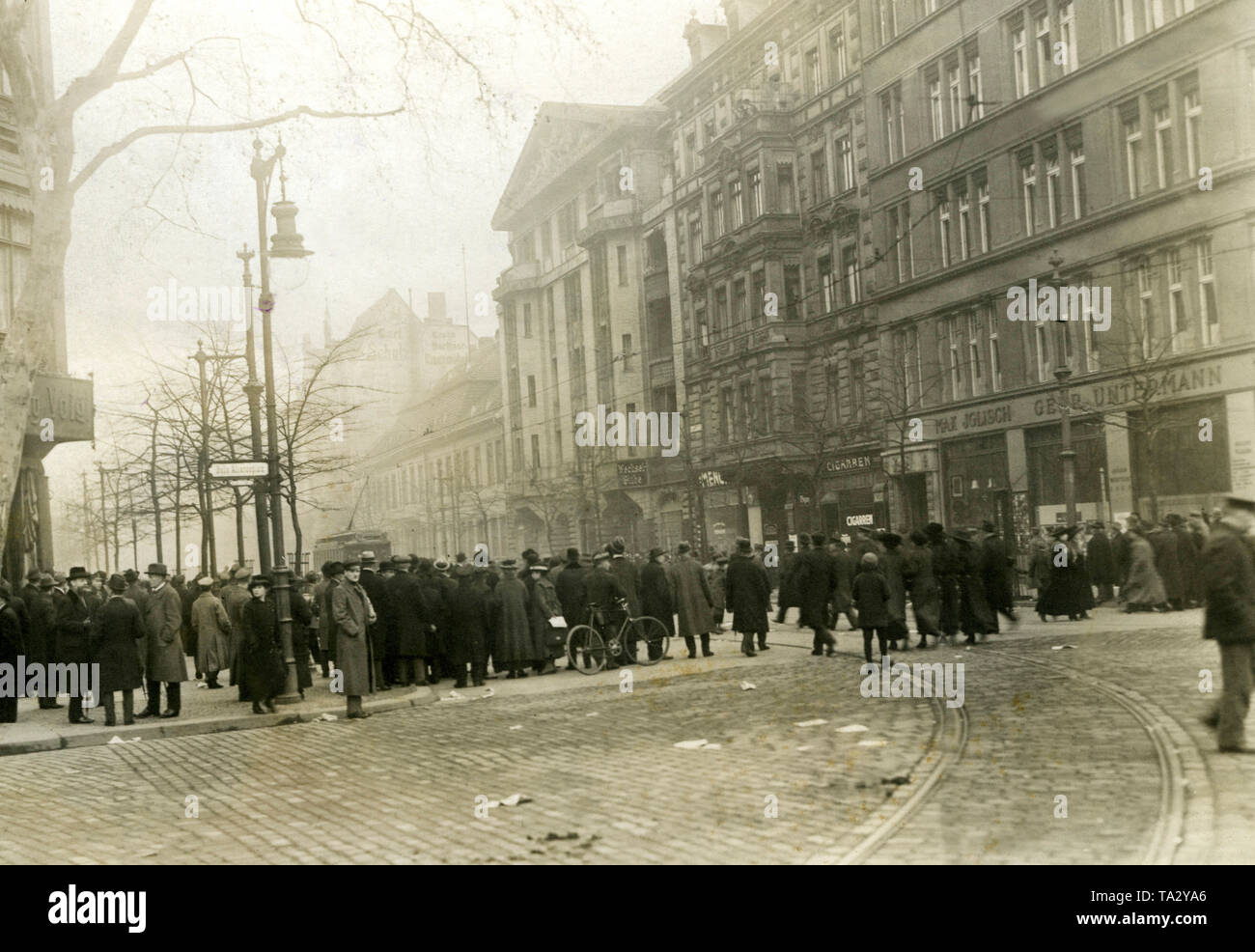 "A group of onlookers observes the events before the ""Vorwaerts building"" in Lindenstrasse. During the January uprising, there were armed conflicts between left-wing revolutionaries and government-loyal Freikorps units in the Berlin Zeitungsviertel (newspaper quarter). Stock Photo"