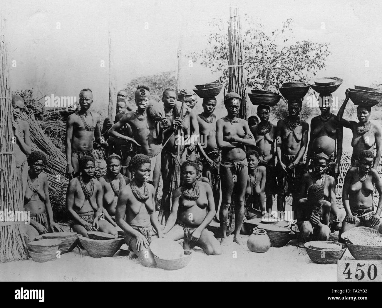 Ovamba women and men with bowls full of grain and cereals in German Southwest Africa (undated photograph with a printed date of the image from 1932). - Stock Image