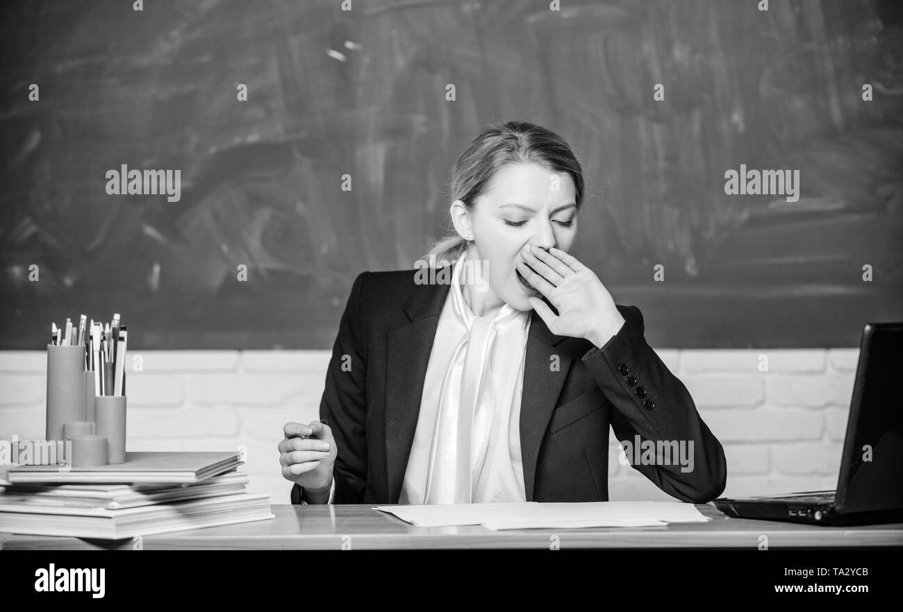 Need for sleep. High level fatigue. Exhausting work in school causes fatigue. Teacher woman sleepy face tired sit table classroom chalkboard background. Life of teacher exhausting. Yawning teacher. - Stock Image