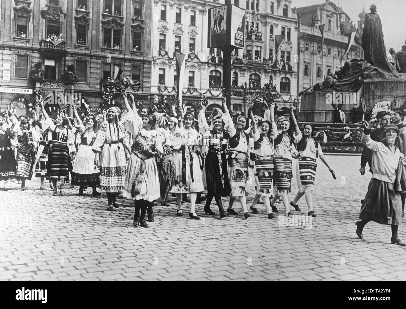 Moravian country girls in traditional costumes at the Sokol Congress in Prague. The girls greet Czechoslovak President Tomas Garrigue Masaryk. A parade takes place in Jan Hus's honor on his birthday. In the background, the Jan Hus Memorial. - Stock Image