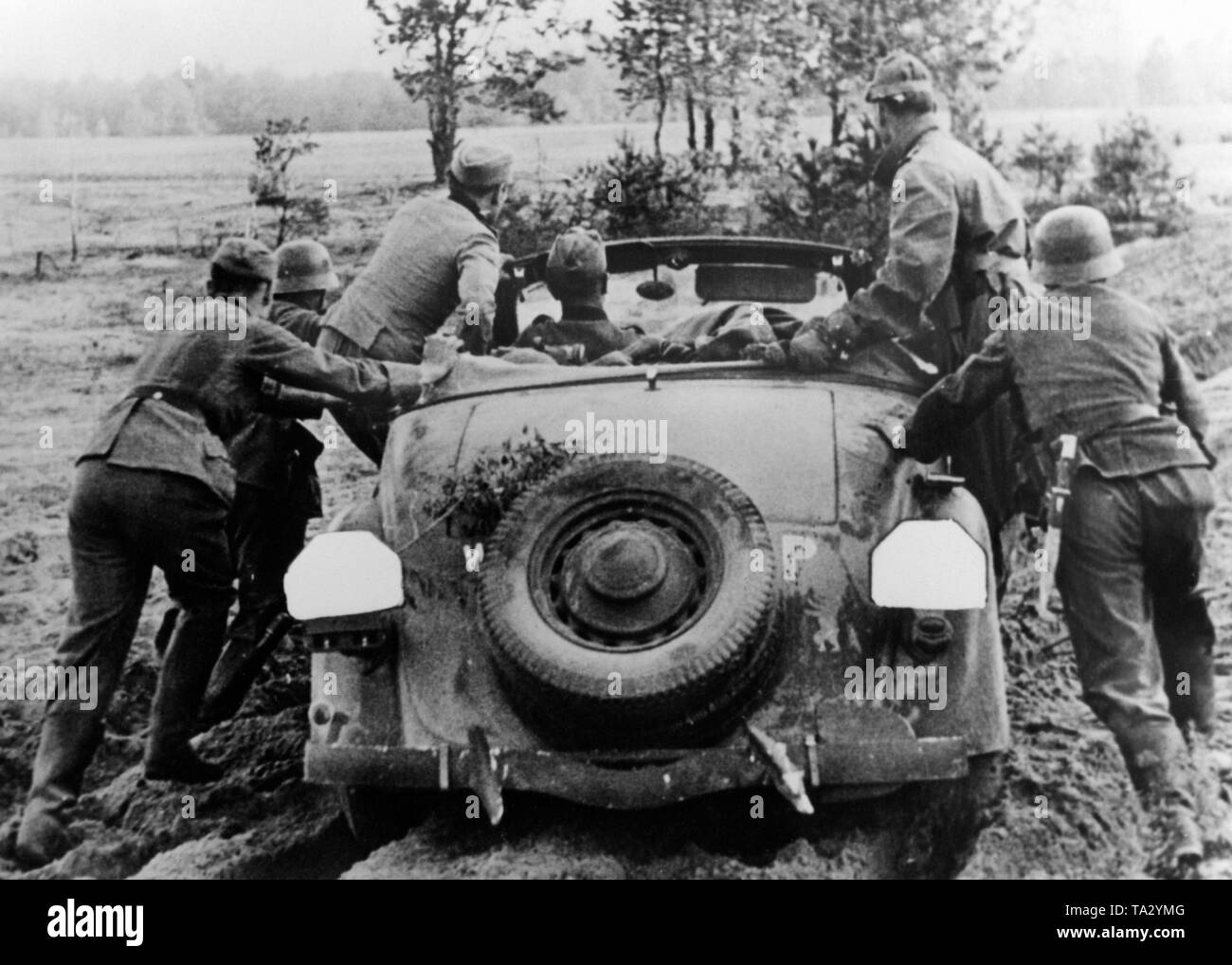 German troops are trying push out a car stuck in a sand pit. Stock Photo
