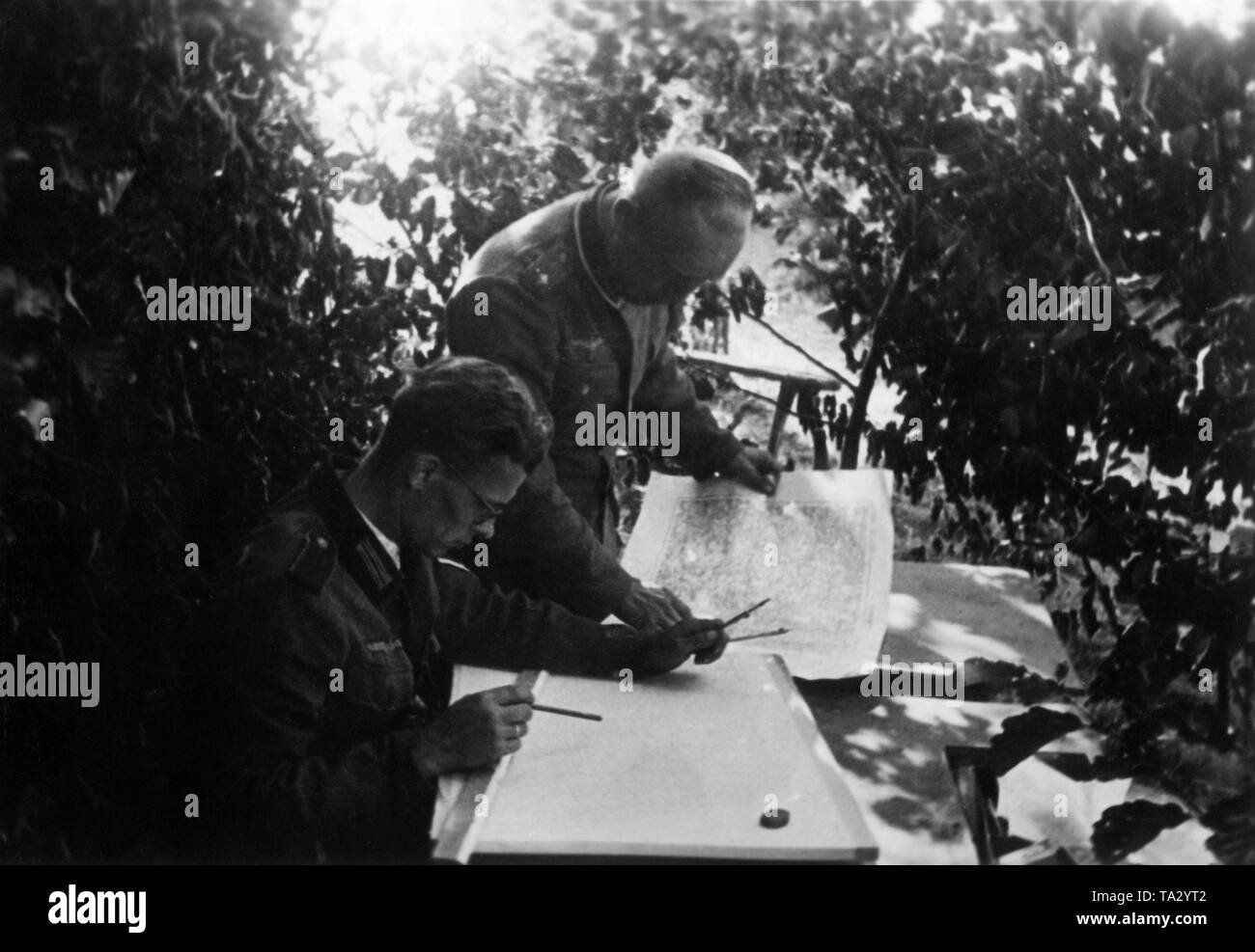 Drawer of a Korpskartenstelle (Corps Map Unit) of the Wehrmacht draws new scout results into existing maps. At Borowka. A lieutenant is sitting in front, a first lieutenant behind him. Photo: war reporter Utecht. - Stock Image