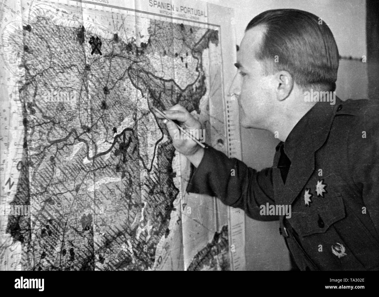 Undated photo of a German major of the Condor Legion, while correcting the new line of the front in a map of the Iberian Peninsula. - Stock Image