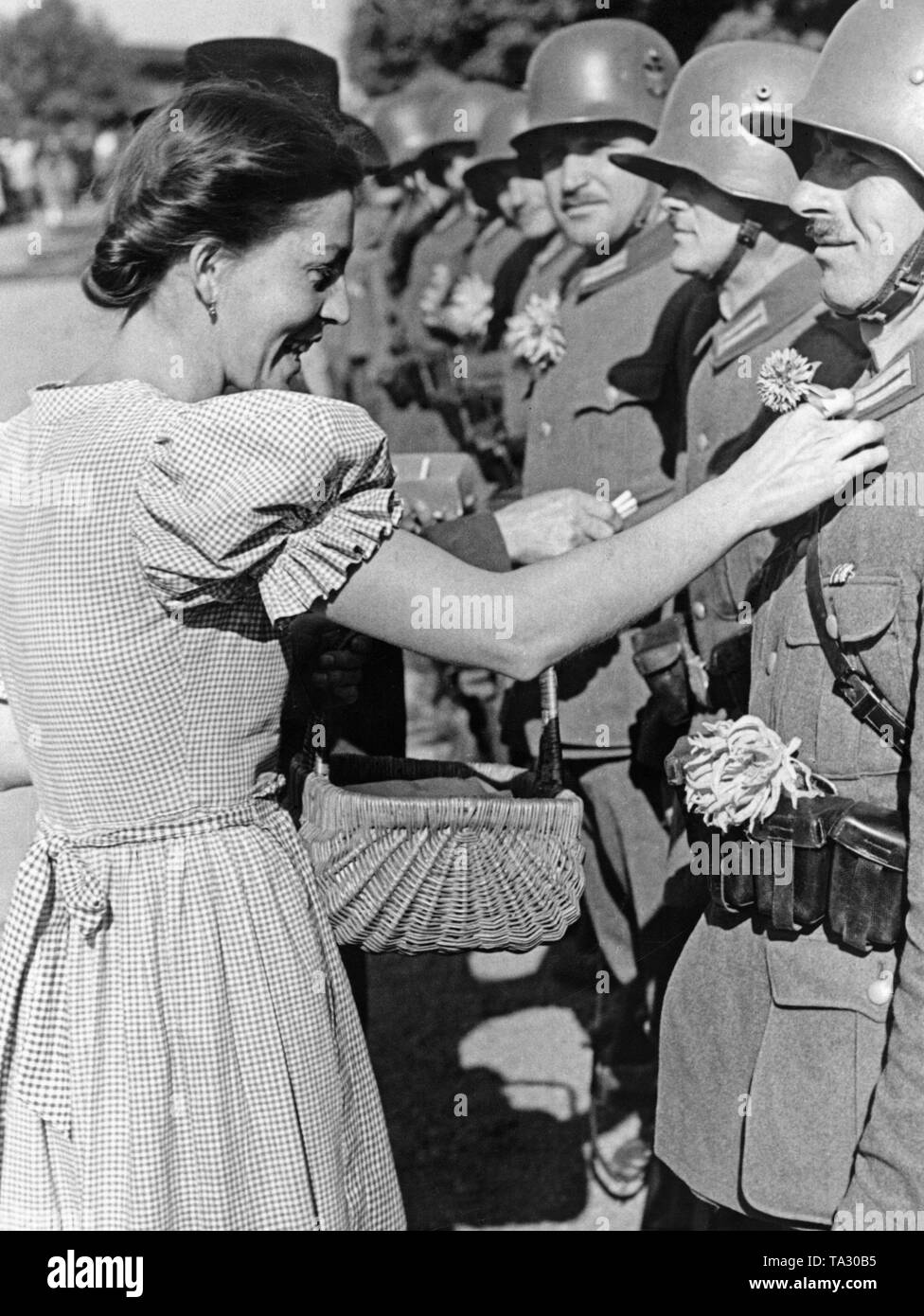 A woman sticks flowers onto the German soldiers' collar in the village of Oberdorf (today Horni Ves) on October 7, 1938 (zone IV). - Stock Image