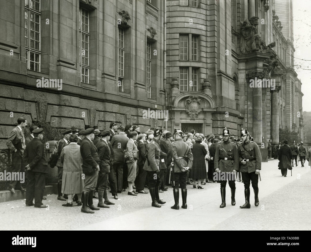 Onlookers are waiting outside the Criminal Court Moabit for the arrival of witnesses. On this day Adolf Hitler was invited as a witness in the Eden Dance Palace trial. - Stock Image