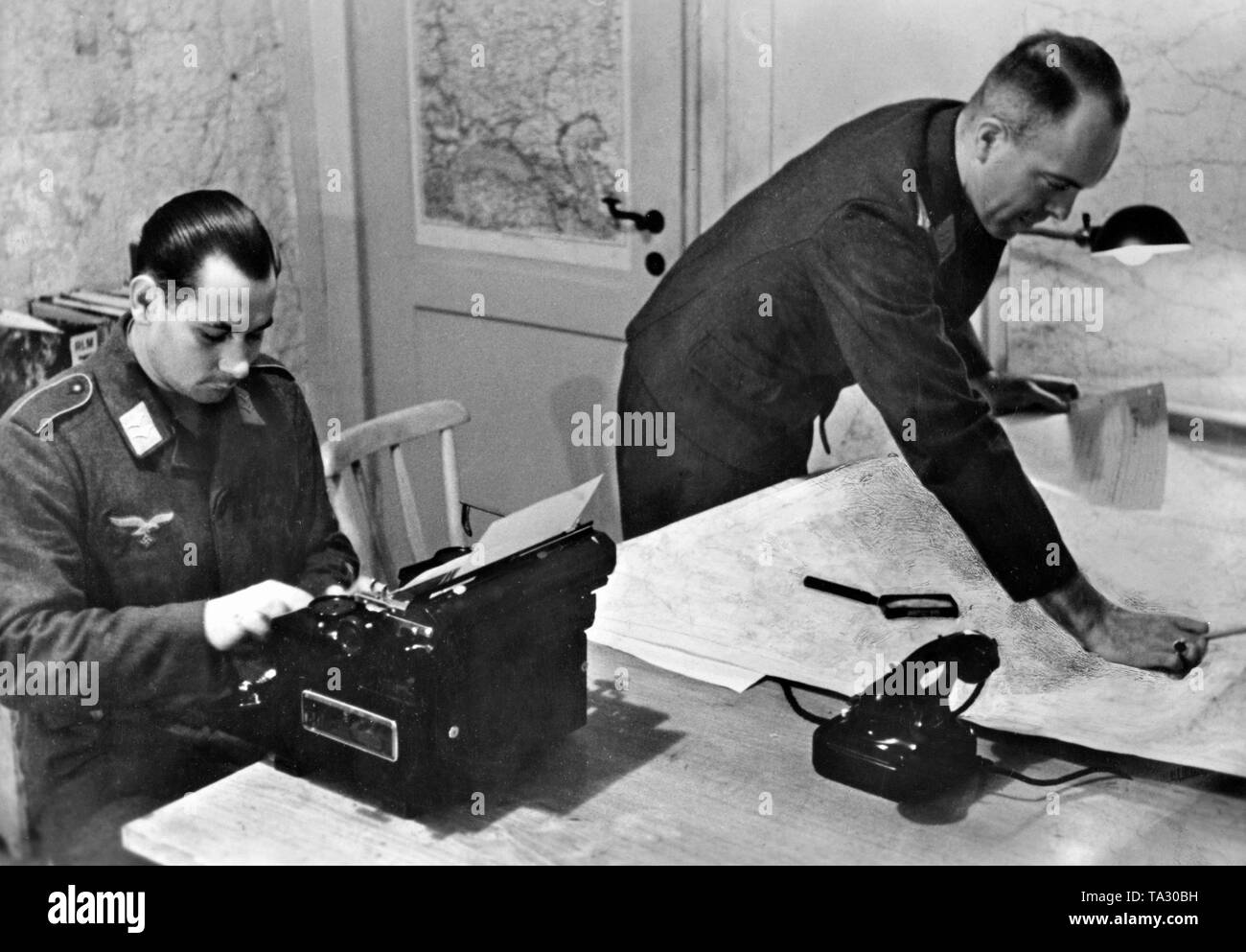 The staff officer of an army group dictates the military situation and the results of the reconnaissance to the typist. Photo: war correspondent Standartenfuehrer Seuffert. Stock Photo
