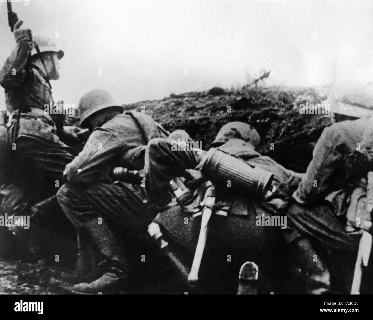 A German battalion in action. With the light gun the sergeant (left) shows to his own combat leaders which position was reached. Stock Photo