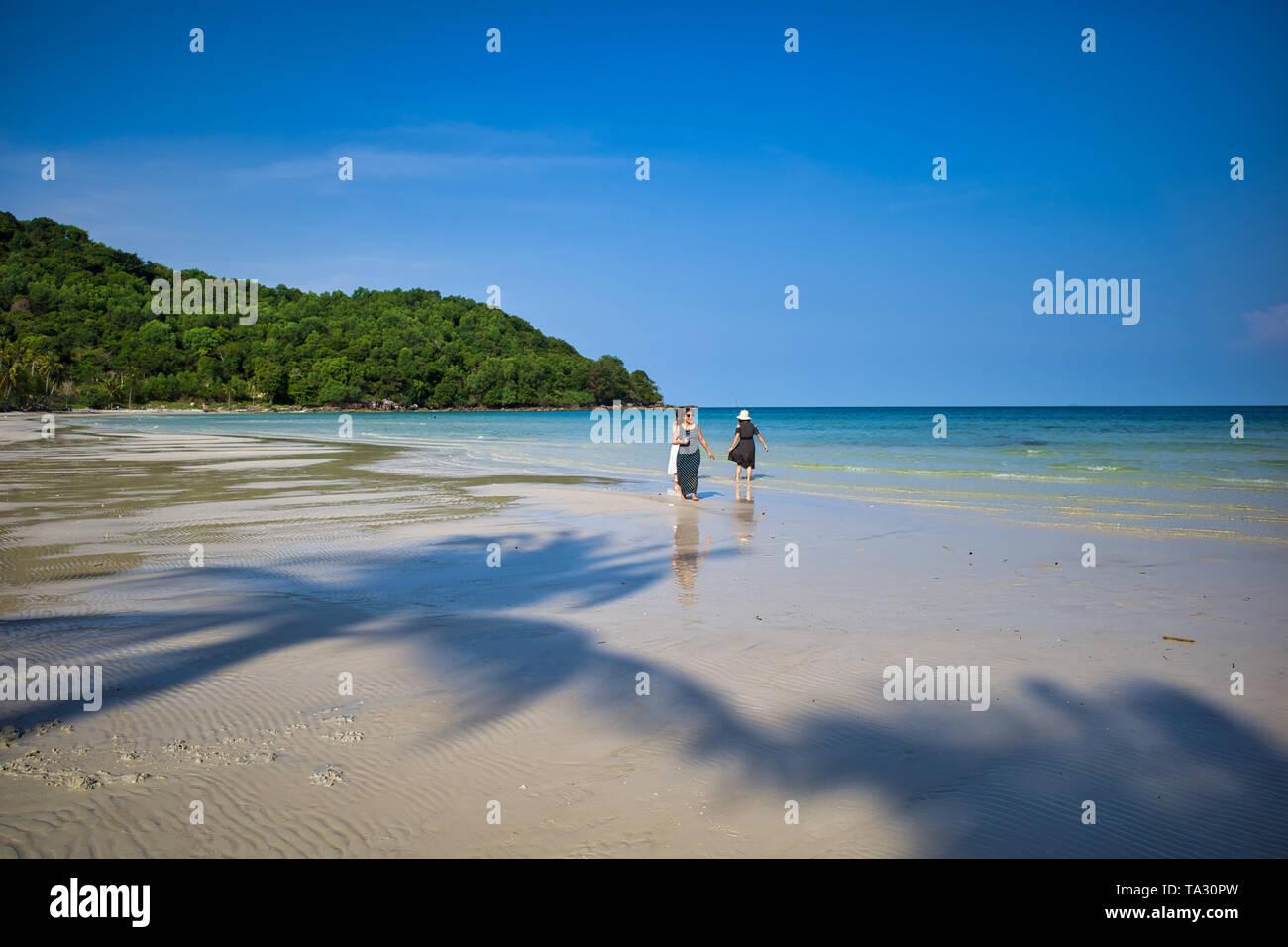 Phu Quoc island, Vietnam - March 31, 2019: White sand beach, sea horizon. Calm sea and girls walking on the beach. Coast of the South China Sea - Stock Image