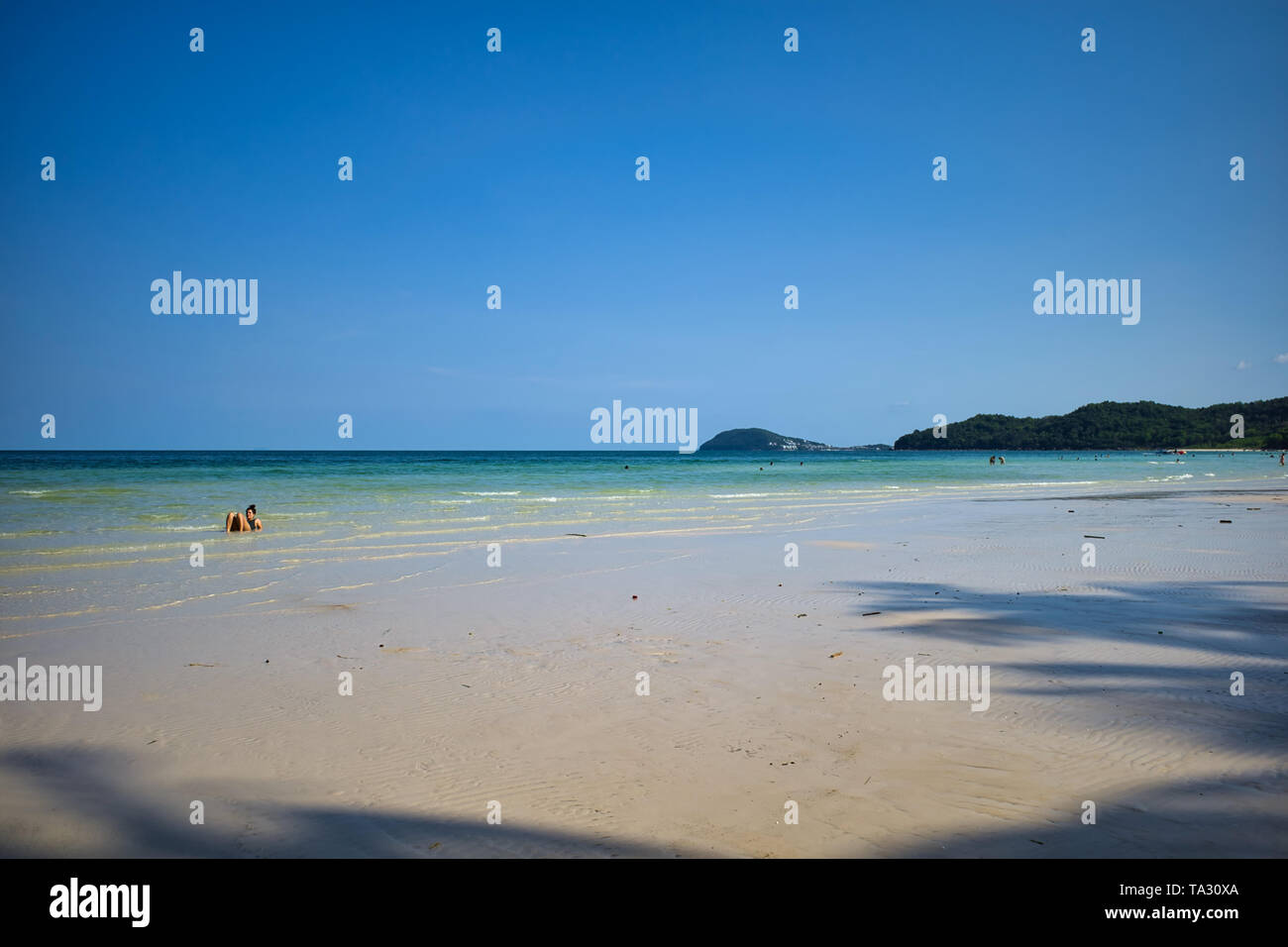 Phu Quoc island, Vietnam - March 31, 2019: White sand beach, sea horizon. Calm sea and girls walking on the beach. Coast of the South China Sea Stock Photo