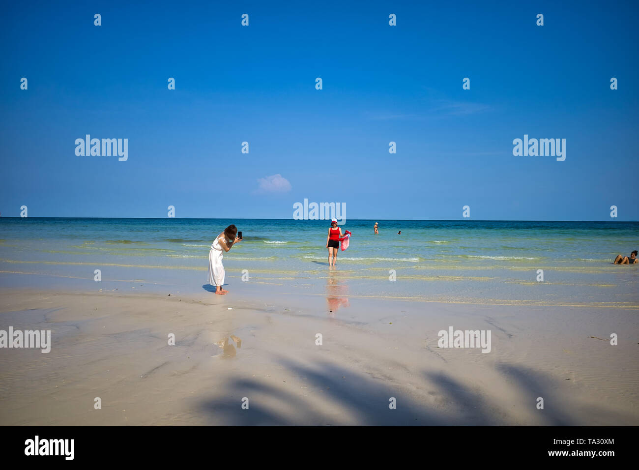 Phu Quoc island, Vietnam - March 31, 2019: White sand beach, sea horizon. Calm sea and girls on the beach are photographed. Coast of the South China S - Stock Image