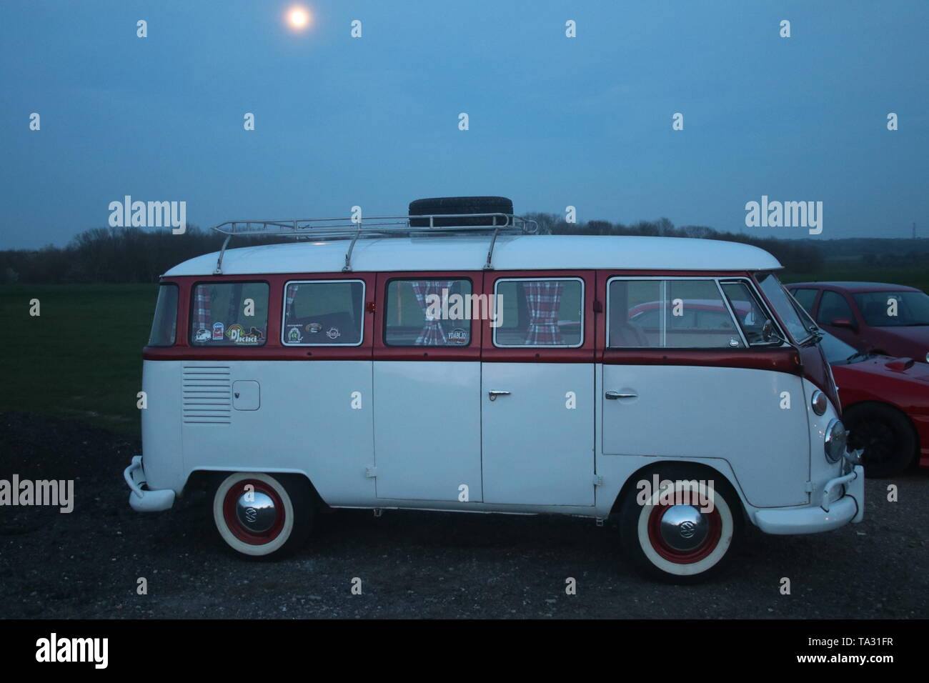 A DUSK SIDE VIEW PHOTO OF A RETRO CLASSIC SPLIT-SCREEN VW VOLKSWAGEN CAMPER BUS VAN WITH SHINING MOON IN SKY ABOVE VEHICLE - Stock Image