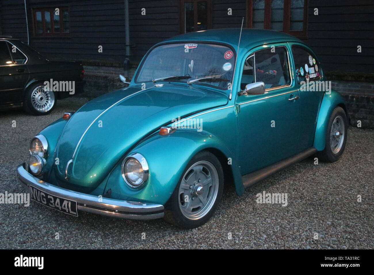 A DUSK PHOTO OF A CLASSIC VW VOLKSWAGEN BEETLE CAR AT A VINTAGE VEHICLE MEET - Stock Image