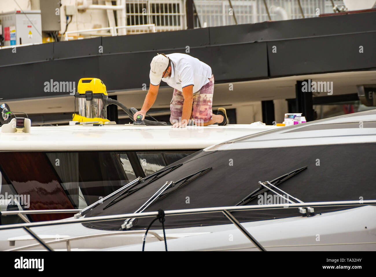 CANNES, FRANCE - APRIL 2019: Person on the roof of a superyacht In Cannes using a power tool to prepare the boat for the spring and summer season - Stock Image