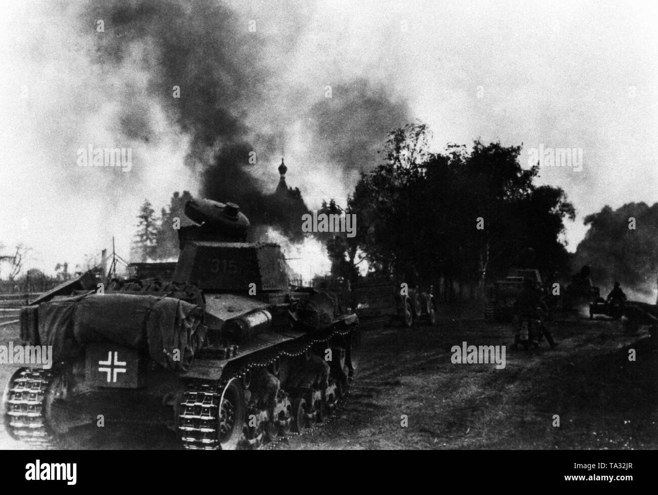 Panzer 35 (t) of the 6th Panzer Division on the advance through a burning village on the eastern front. Area Army Group North. Stock Photo
