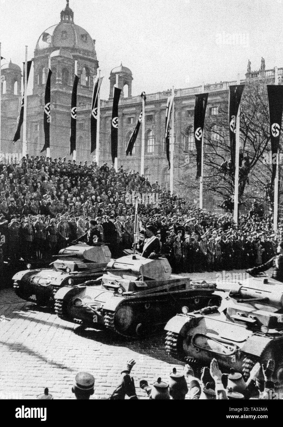 Tanks drive in front of Adolf Hitler on the Heldenplatz in Vienna. A military parade takes place on the occasion of the Anschluss (annexation) of Austria to the German Reich. Around Hitler stand prominent German and Austrian generals. - Stock Image