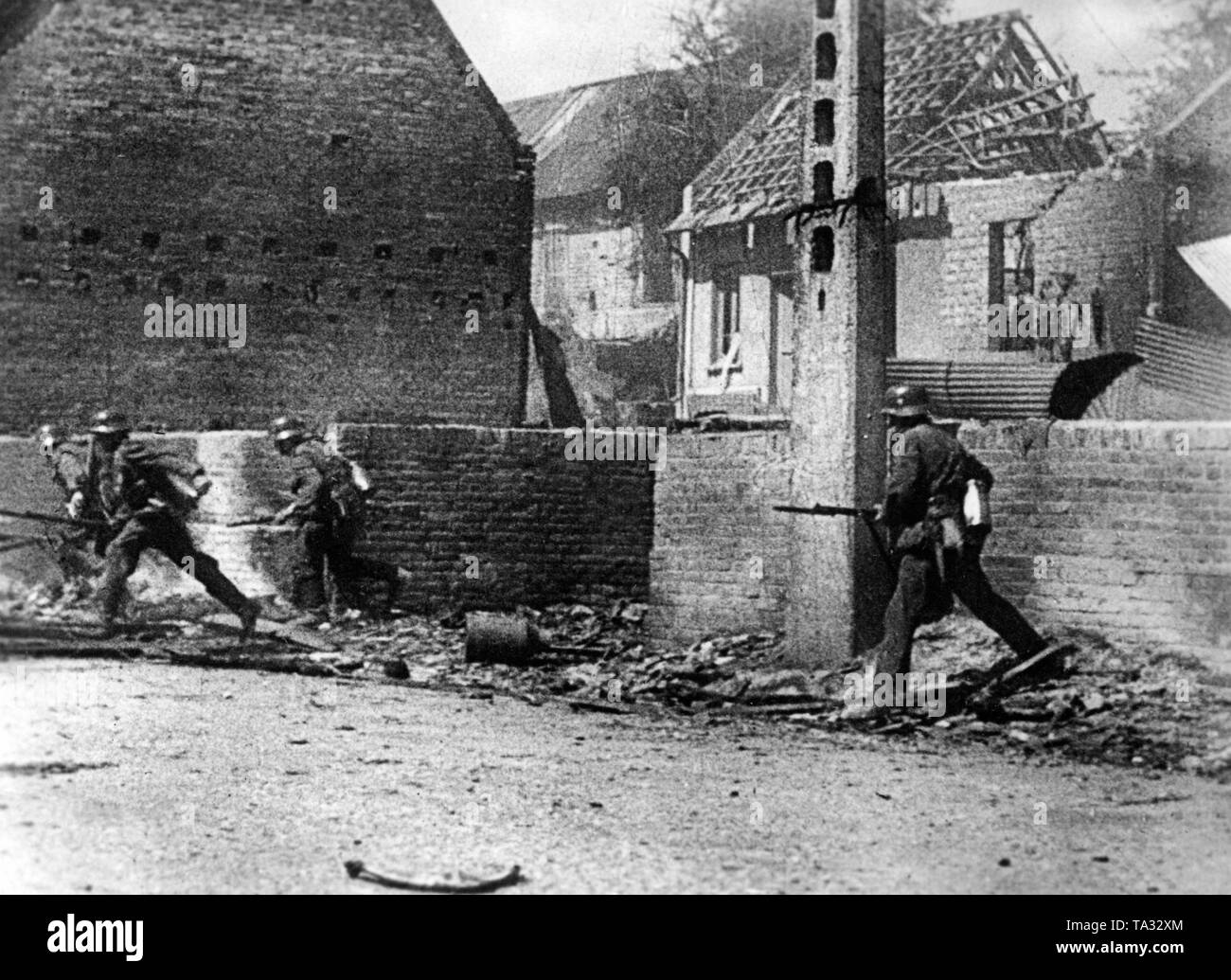 A group of German infantrymen are walking along a street during the fighting for a French village. Stock Photo