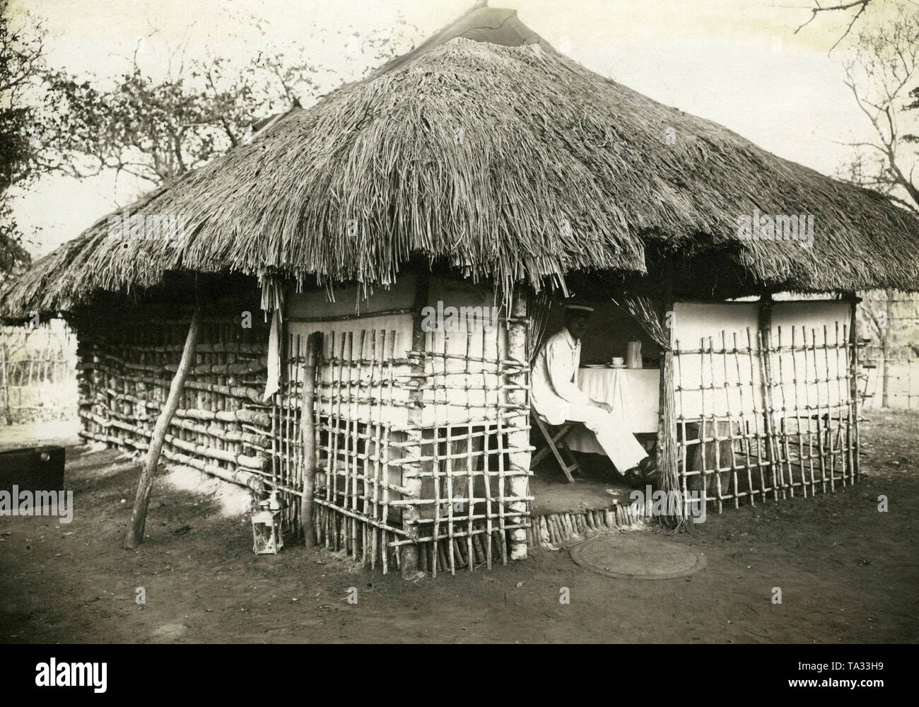 A white man, possibly a colonial officer, sitting at the coffee table in a house built in local style in the German colony of German East Africa. - Stock Image