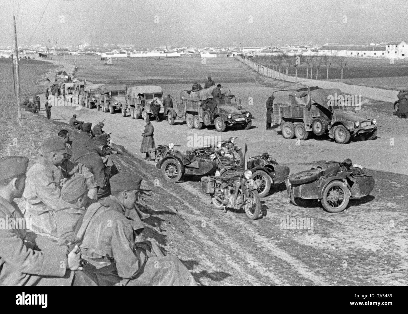 An antiaircraft battery of the German Condor Legion takes rest on a road at Toledo during the last battles of the Spanish Civil War on March 28, 1939. On the right in the foreground, Kradschuetze (motorcycle mounted infantrymen) are having a rest. Their motorcycles of the type BMW R12 (partly with sidecar) are parked on the roadside. Behind, a convoy of trucks of the type Krupp L2 H143. - Stock Image