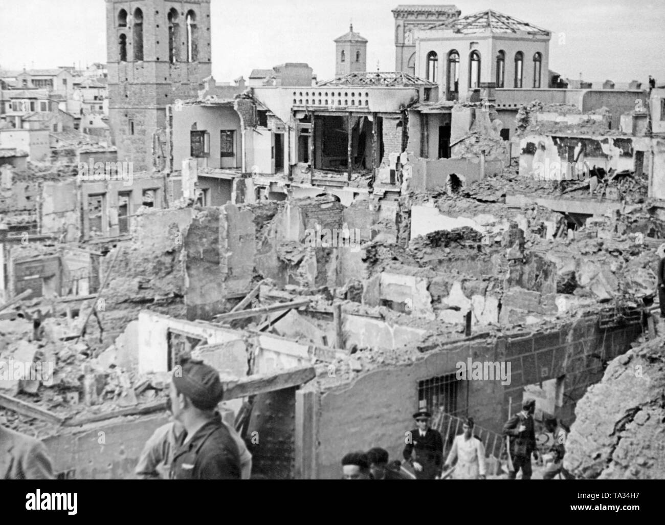 Spanish soldiers visit the patio of the liberated Alcazar of Toldeo after its conquest on September 26, 1936. In the background, destroyed houses in the neighbourhood of the fortress. - Stock Image