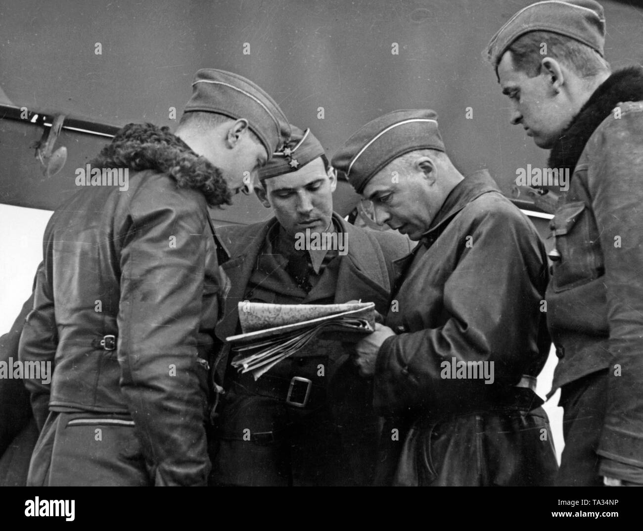 Photo of a briefing of fighter pilots with a commander (center, with a map) of a squadron of the Condor Legion under a wing of an airplane. - Stock Image
