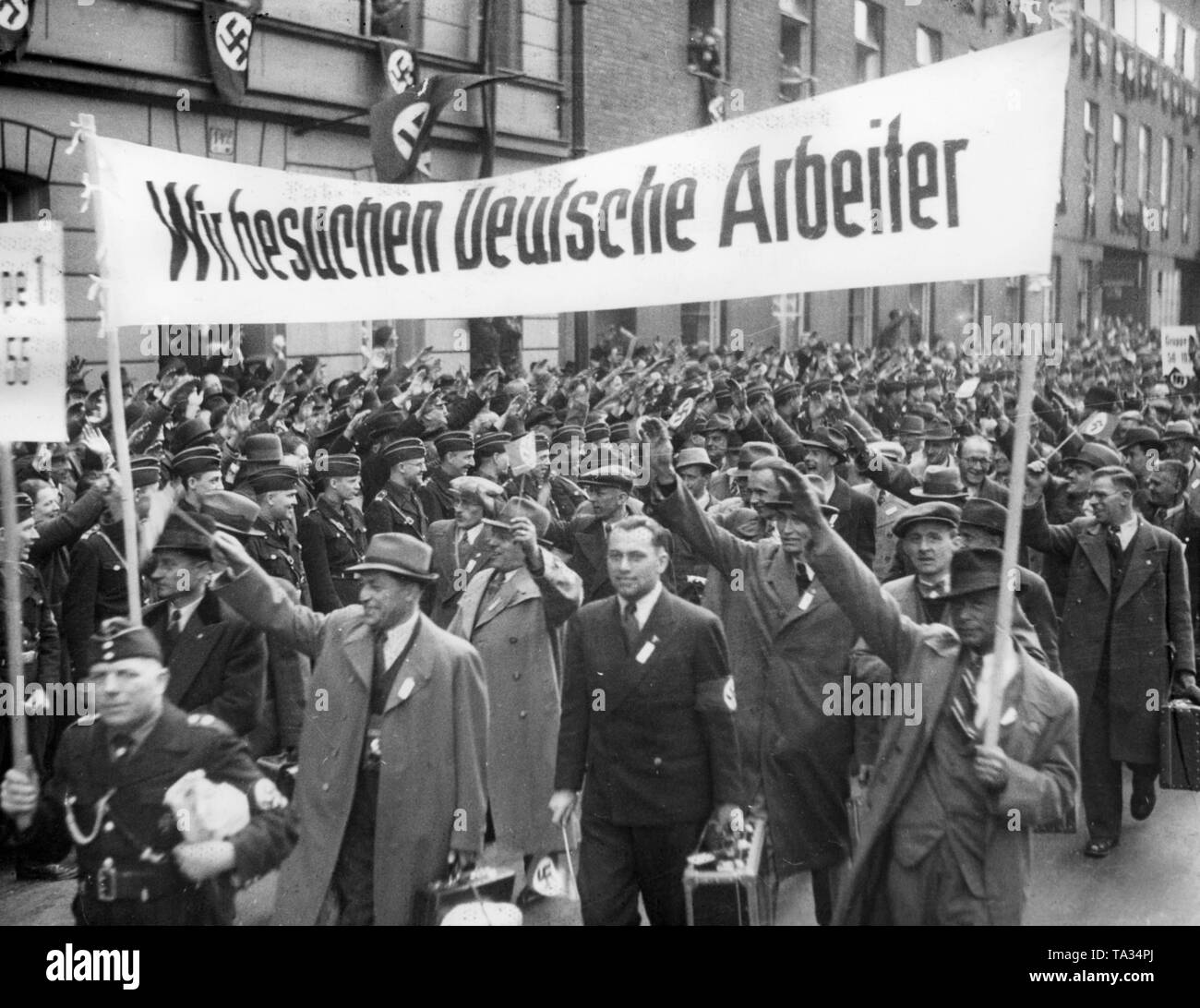 After the Anschluss of Austria, 2000 Viennese workers arrived with special trains at the Anhalter Bahnhof in Berlin for a trip organized by the Nazi organization 'Kraft durch Freude' ('Strength through Joy'). Here they are marching to their quarters. In the front, a banner with the inscription 'We are visiting German workers'. - Stock Image