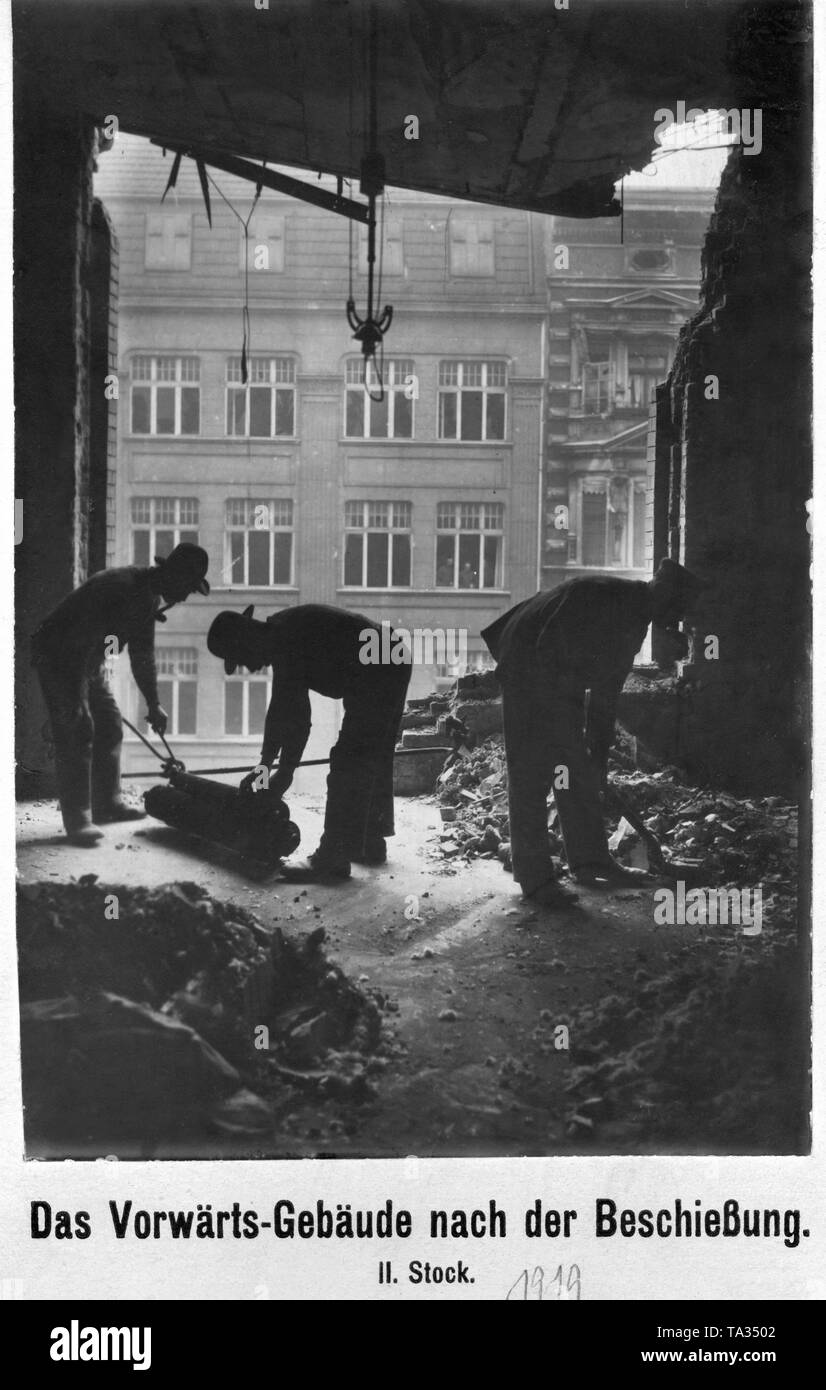 """Repairing the damage caused by the fights in the """"Vorwaerts-building"""". During the January uprising, there were armed conflicts between left-wing revolutionaries and government-loyal Freikorps units in the Berlin Zeitungsviertel (newspaper quarter). Stock Photo"""