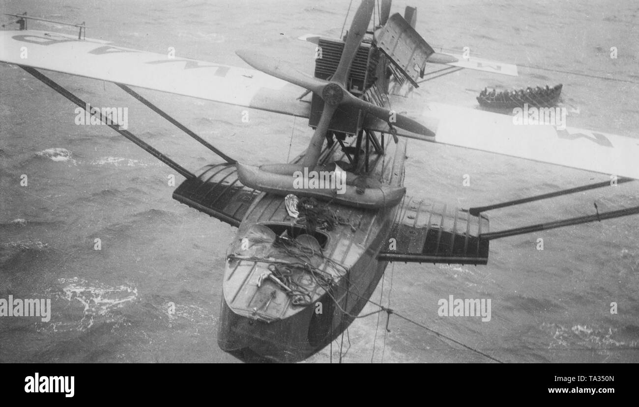 The seaplane 'Numancia' with the tail number M-Mwap is heaved aboard the HMS Eagle. In the background in a lifeboat are Spanish pilots who have been rescued by the crew of the Eagle. On June 22, 1929 the Spanish pilot Ramon Franco failed with the attempt to cross the Atlantic and was rescued seven days after the emergency water landing by the British aircraft carrier HMS Eagle. - Stock Image